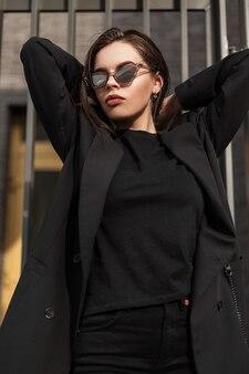 Девушка в модной черной повседневной молодежной одежде. современная молодая женщина в модном пиджаке в стильной черной футболке стоит на улице в городе. винтажный черный наряд для женщин.