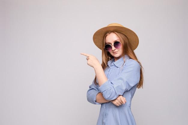 何かを指している流行の服の女の子。