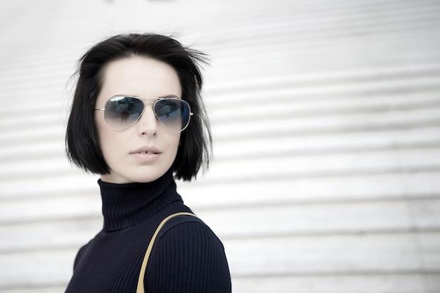 Девушка в модных очках на открытом воздухе. красота и городская мода. облик и городской стиль. поза фотомодели на фоне лестницы. деловая женщина со стильными короткими волосами брюнетки, копией пространства