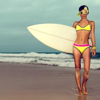 サーフボードとビーチに立っているファッショナブルな水着の女の子。