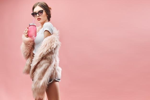 フェイクピンクの毛皮のコートの黒のショートパンツの白いトップとサングラスの女の子は目を閉じてピンクの飲み物を保持しています...