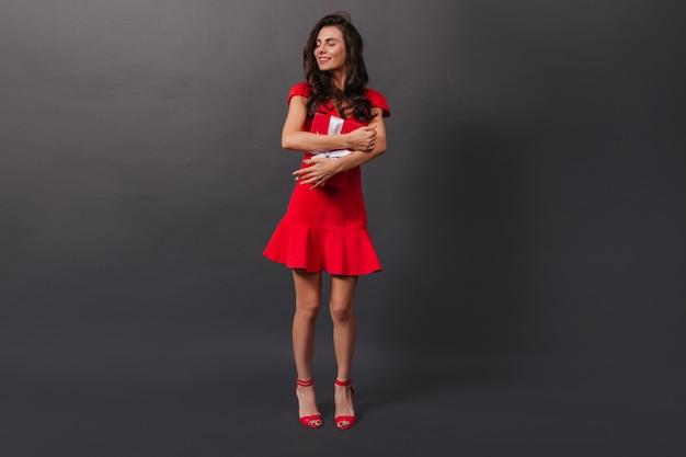 축제 분위기의 소녀는 선물로 빨간색 상자를 포용합니다. 격리 된 검은 배경에 포즈 세련 된 드레스에 여자.