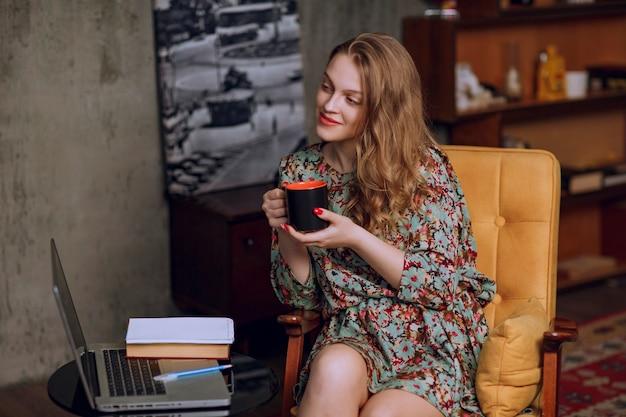 茶色のコーヒーマグを座って保持している花柄のドレスの女の子。