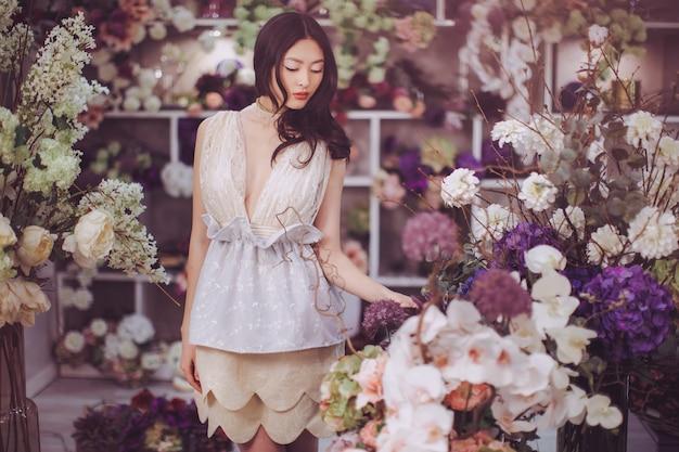 Девушка в цветочном магазине. женщина, стоящая против цветочного боке в цветочном магазине. радостная азиатка