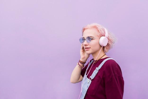 Девушка в очках и наушниках слушает музыку на фоне фиолетовой стены