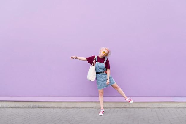 Девушка в очках и джинсах с покупателем в руках на фоне фиолетовой стены