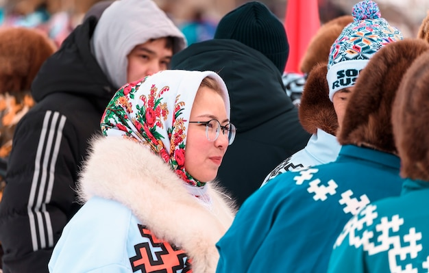Девушка в очках в толпе людей. праздник дня северного оленя народов севера.