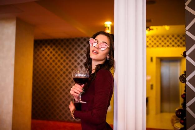 와인 한 잔과 안경에 소녀입니다.