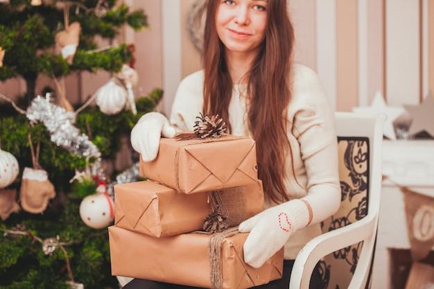 クリスマスツリーの近くで彼女の膝にギフトボックスを保持している手袋の少女