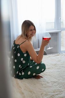 레드 와인 한 잔 함께 침대에서 녹색 잠옷 소녀. 침대에서 모닝 와인. 세로 사진