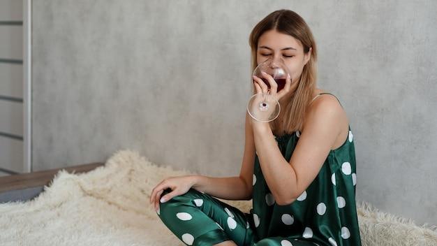 赤ワインのグラスとベッドで緑のパジャマを着た女の子。ベッドでの朝のワイン
