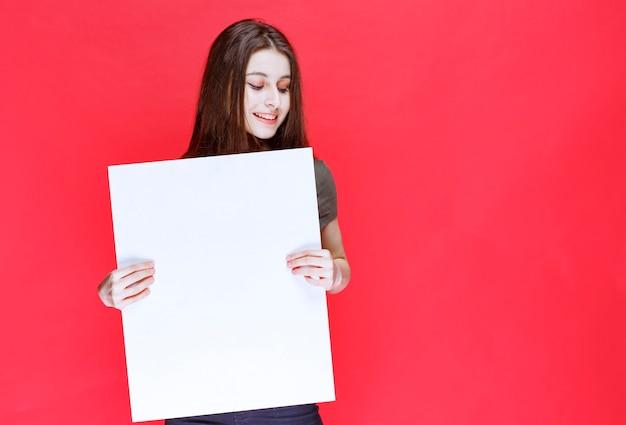 Девушка в зеленой рубашке держит большой пустой квадратный информационный стол.