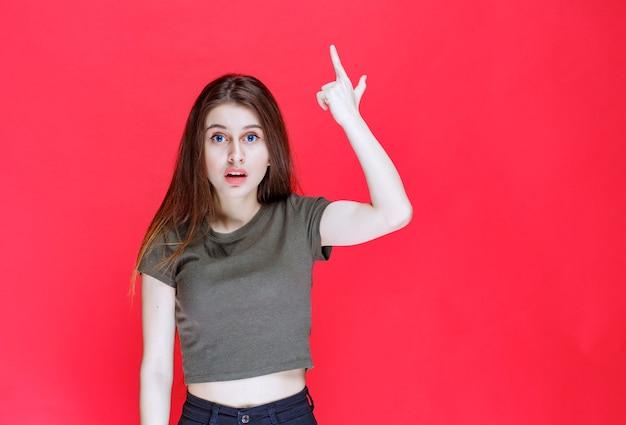 위의 뭔가 가리키는 녹색 셔츠에 소녀입니다. 무료 사진