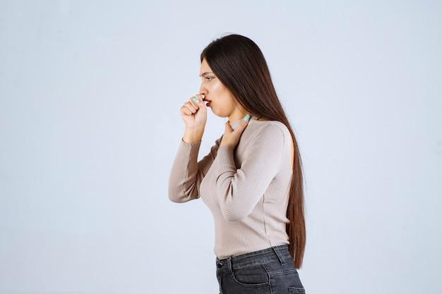 회색 셔츠를 입은 소녀가 목이 아프다.