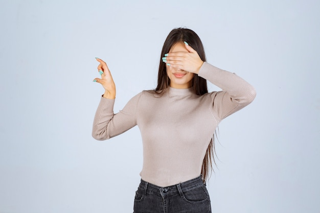 손으로 그녀의 얼굴을 닫는 회색 셔츠에 소녀.