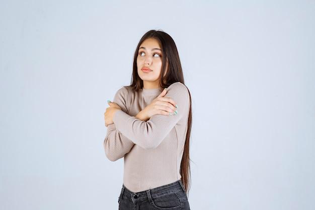 Девушка в серой рубашке мерзнет.