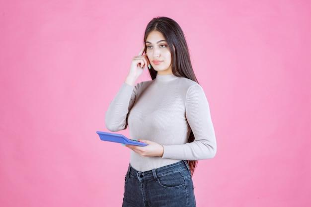 青い電卓を持って詳細を考えている灰色のシャツの女の子