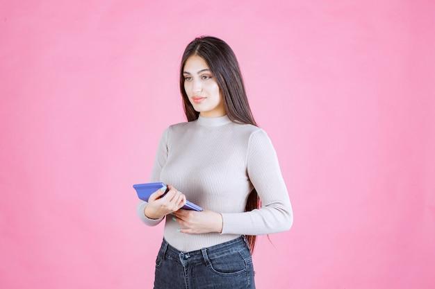 Девушка в серой рубашке держит синий калькулятор, смотрит и работает с ним