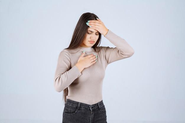 Девушка в серой рубашке держится за голову из-за головной боли.
