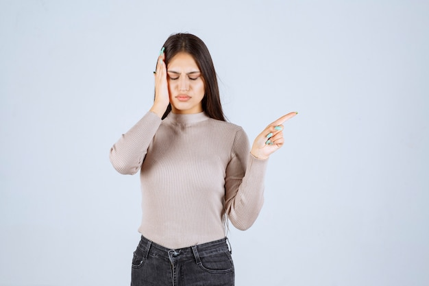 頭痛のために頭を抱えている灰色のシャツを着た女の子。