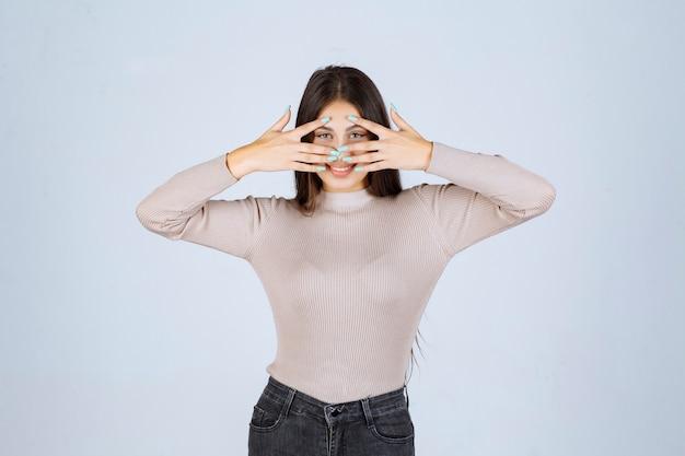 指を通して見ている灰色のシャツの女の子。 無料写真