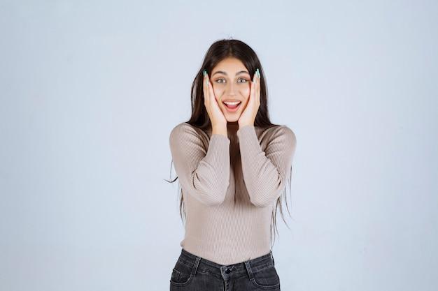 灰色のシャツを着た女の子は興奮して驚いたように見えます。