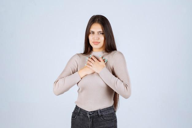 Девушка в серой рубашке выглядит напуганной и напуганной.