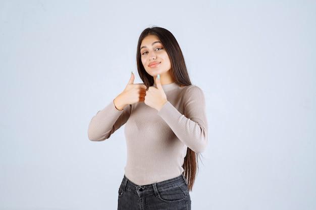 가입 엄지 손가락을 만드는 회색 셔츠에 소녀입니다.