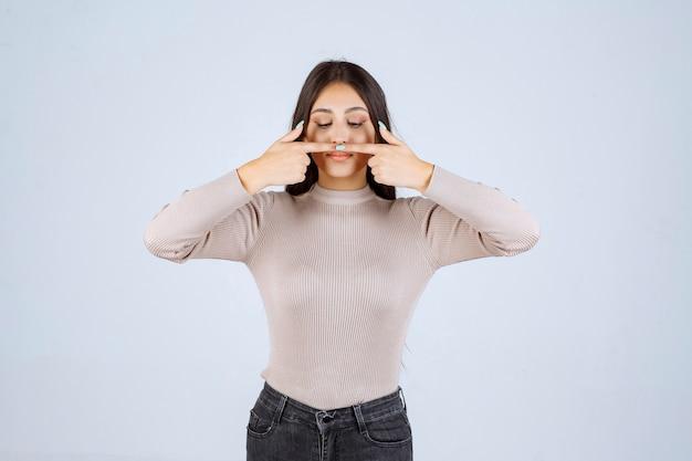 Девушка в серой рубашке, указывая на ее рот.