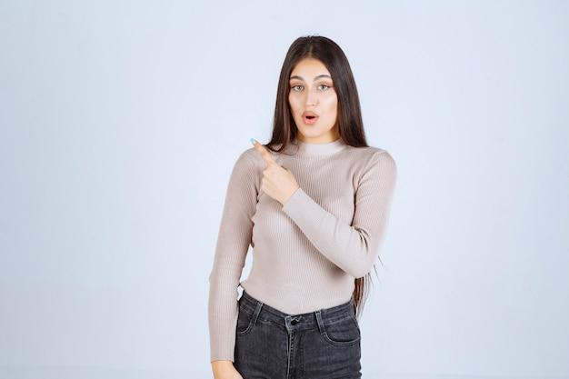 왼쪽에 뭔가를 가리키는 회색 셔츠에 소녀.