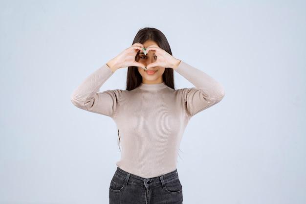 ファンに愛を送る灰色のシャツを着た女の子。