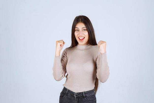 彼女の腕の筋肉を示す灰色のシャツの女の子。