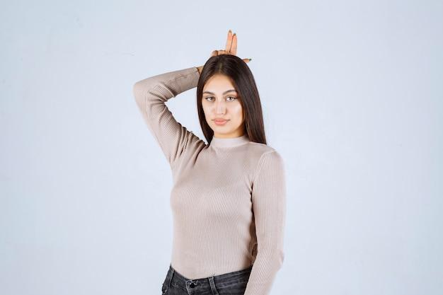 ウサギの耳のサインを示す灰色のシャツの女の子。
