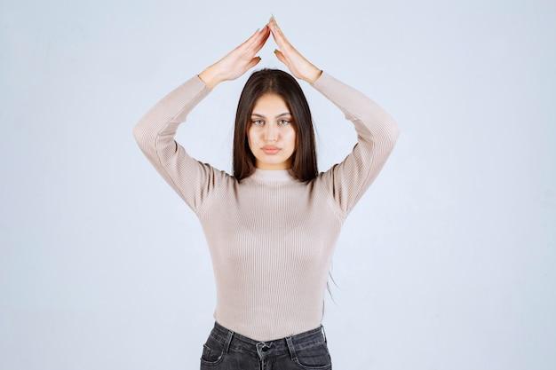 屋根または三角形を示す灰色のシャツの女の子。