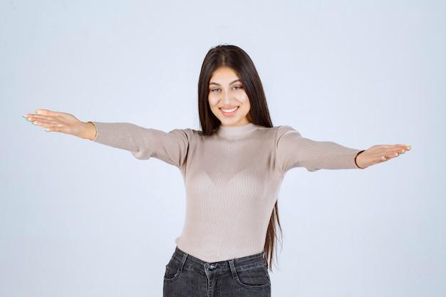 Девушка в серой рубашке показывает что-то в руке.