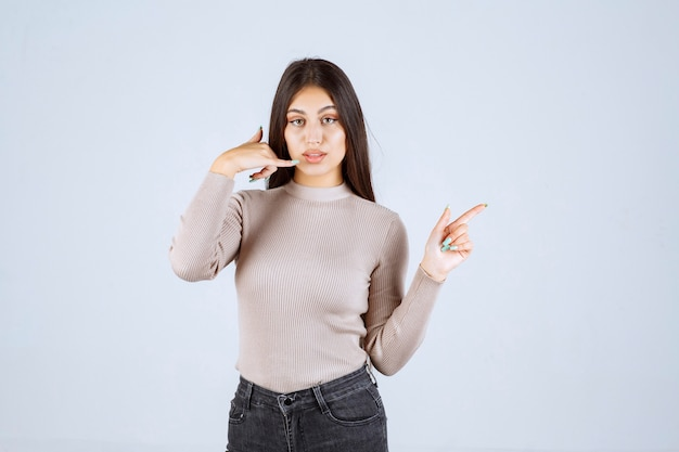전화를 요청하는 회색 스웨터에 소녀입니다.