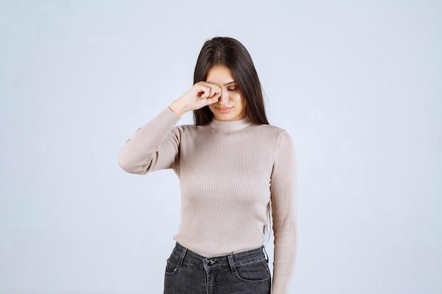 Девушка в сером свитере плачет.