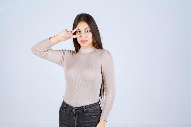 평화 손 기호를 하 고 회색 스웨터에 소녀입니다.