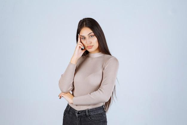 Девушка в сером свитере дает противные и соблазнительные позы.