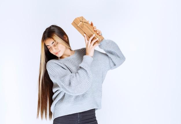 Девушка в сером свитере держит картонную подарочную коробку.