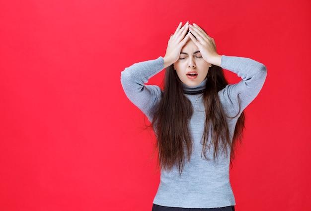 灰色のセーターを着た女の子は非常に恐ろしくて混乱しているように見えます。