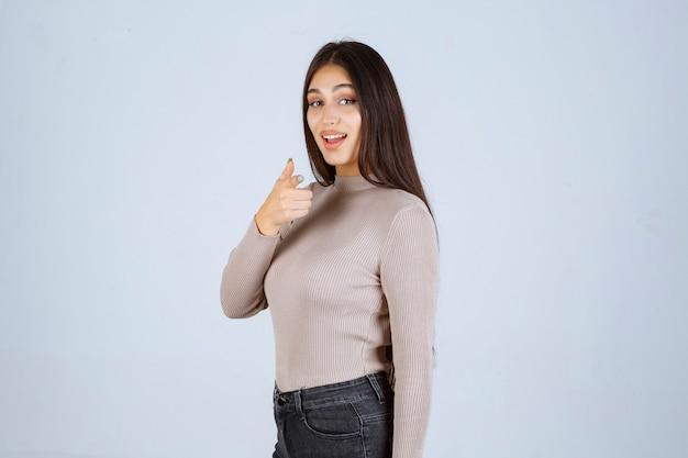 Девушка в сером свитере, делая большой палец вверх знак.