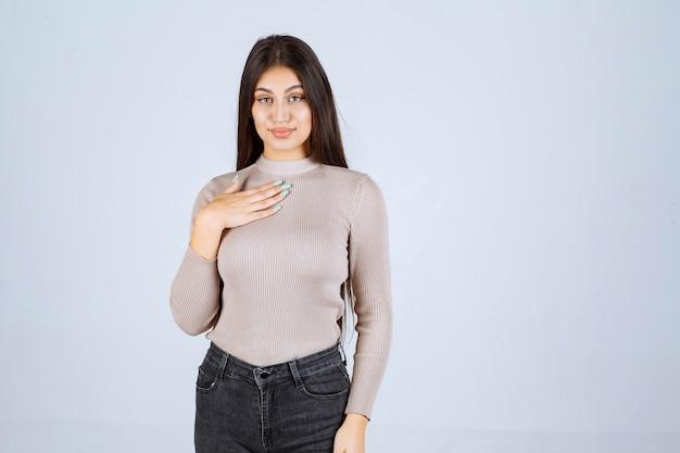 자신을 가리키는 회색 스웨터에 소녀입니다.