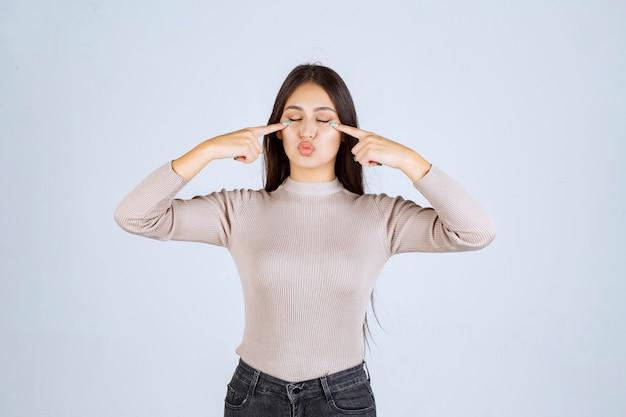 Девушка в сером свитере, указывая головой.