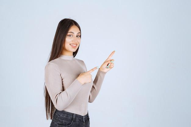 上に何かを指している灰色のセーターの女の子。