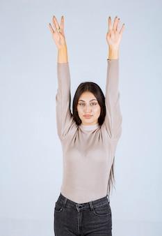 그녀의 손을 키우는 회색 스웨터에 소녀입니다.