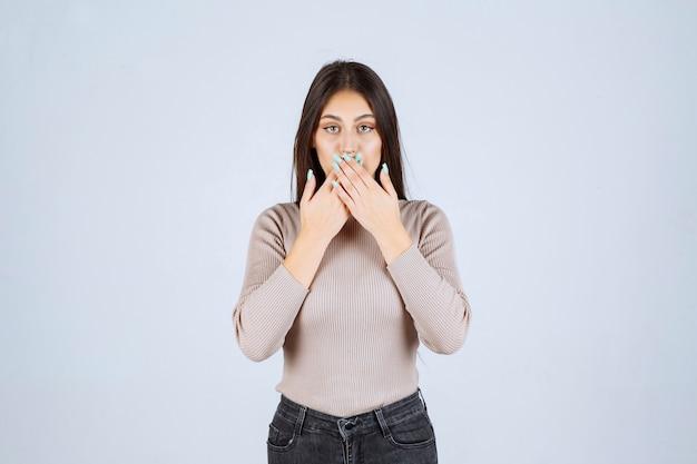 キスを送信する灰色のセーターの女の子。