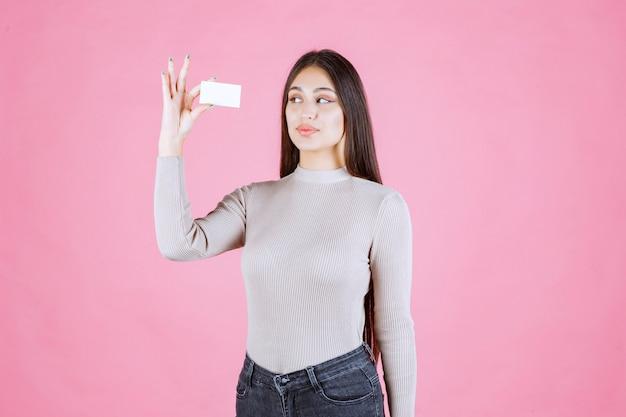 彼女の名刺を見せて提示する灰色のセーターの女の子
