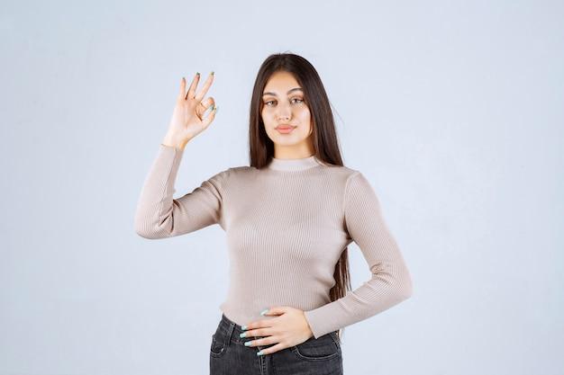 Девушка в сером свитере, показывая знак ок круга.
