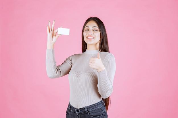 Девушка в сером свитере показывает свою новую визитную карточку, делая хороший знак рукой